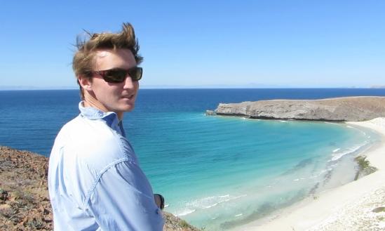 Robert on a cliff overlooking a sandy beach