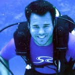 Jeff scuba diving smiling while holding regulator