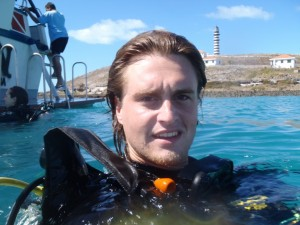 upper body photo of Matthew Haggerty at the surface of the water in scuba gear with a dive boat and lighthouse in the background
