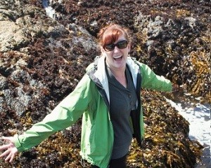 upper body photo of Sadie Small standing in the rocky intertidal with arms outstretched