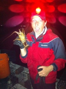 woman in red jacket holding a lobster in the dark with a red light coming from a headlamp