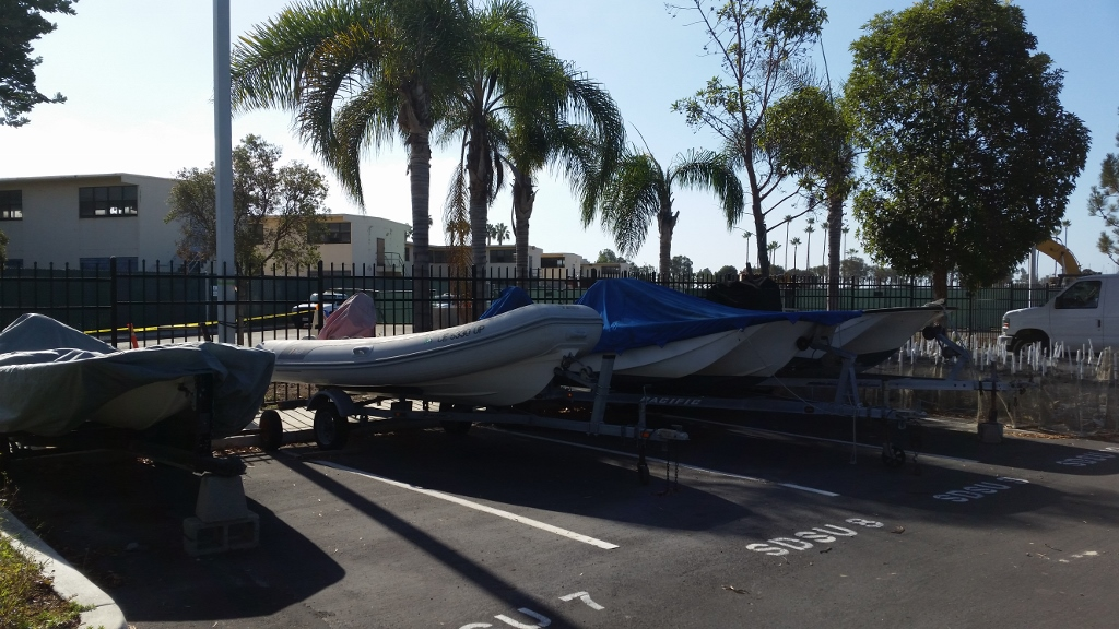 4 boats on trailers parked in an asphalt parking lot