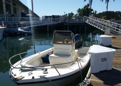 21' open bow, center console driven boat docked at on a floating pier