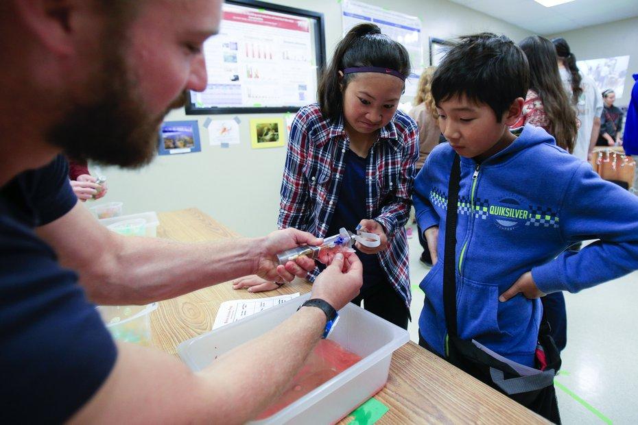 man shows two children a handheld scientific instrument